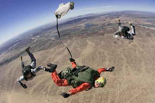 due istruttori e un allievo in volo durante lezione pratica di paracadutismo