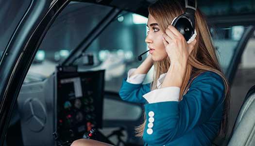 pilota donna in cuffia in cabina elicottero